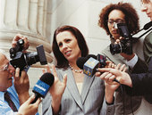 reporters interview woman on professional attire outside the courthouse