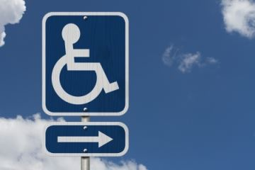 International wheelchair symbol of access with blue sky background