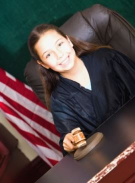 smiling female judge wearing black court robes holds gravel