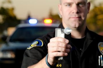 male police officer holds alcohol measurement device with police car in the background