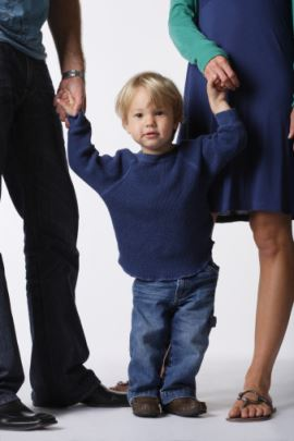 blonde boy holds hands with adult male and female