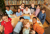 female educator surrounded by ethnically diverse children at school table